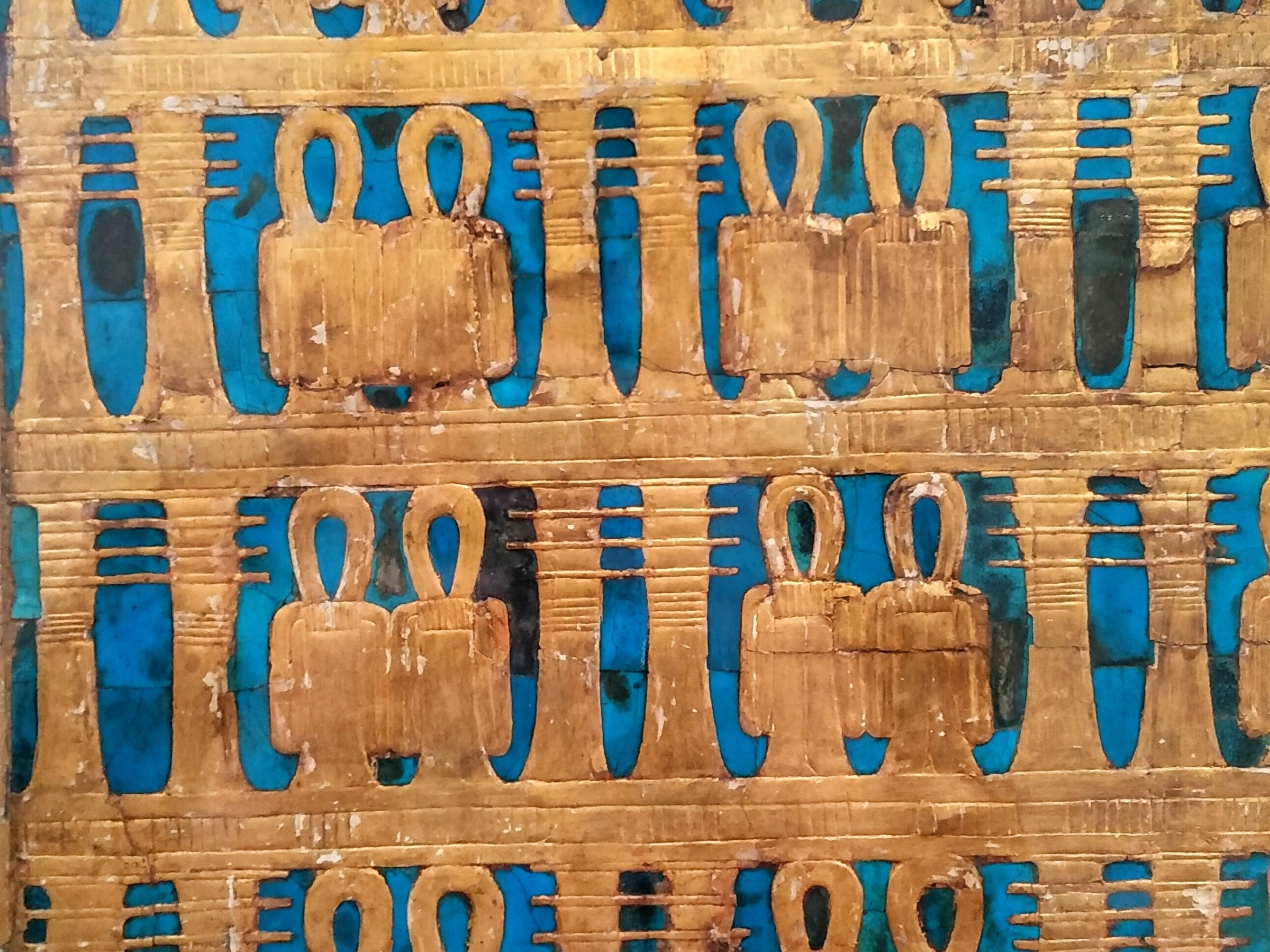 The side of a gold and turquoise coffin in the Cairo museum