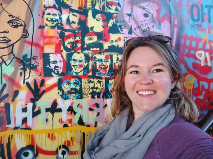 Emma standing in front of some graffiti art on the MONA Ferry