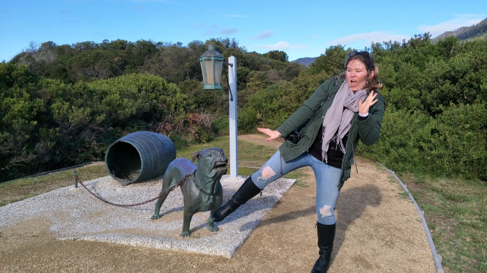 Emma pretending to be scared of a statue of a dog at Eaglehawk Line