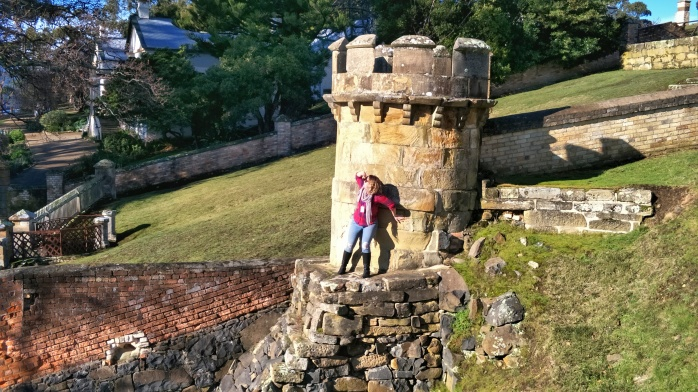Emma standing on a ledge, leaning back against a guard tower at port Arthur