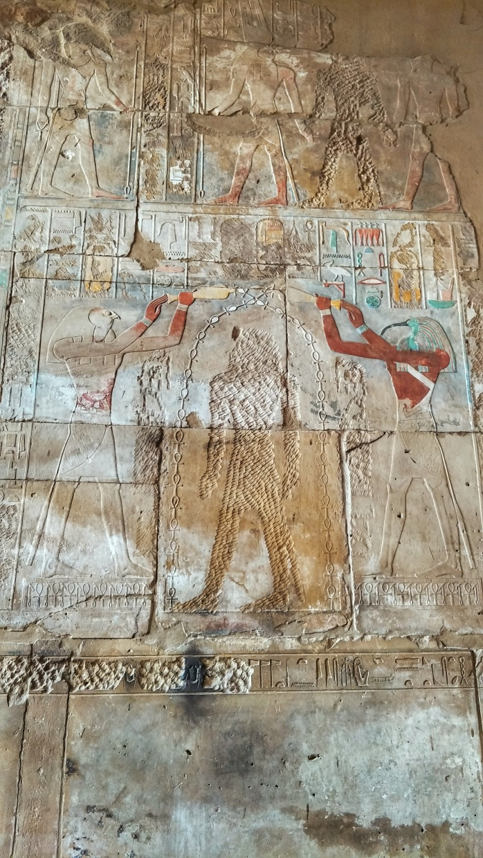 A coloured carving of an Egyptian pharaoh and gods.