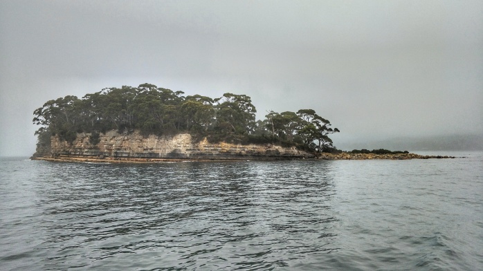 Point Puer Boys Prison surrounded by ominous grey clouds and deep water