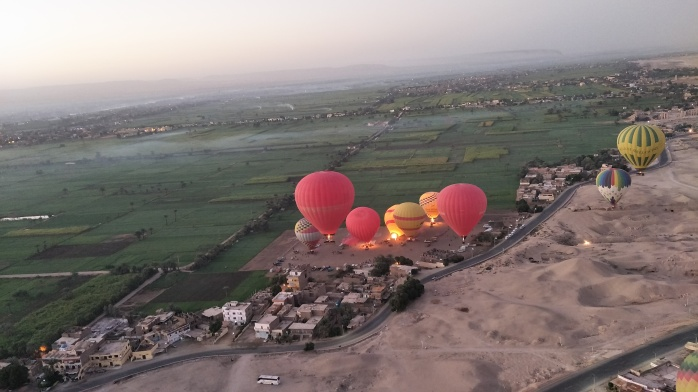 Hot-air ballooning over The Valley of the Kings at sunset.