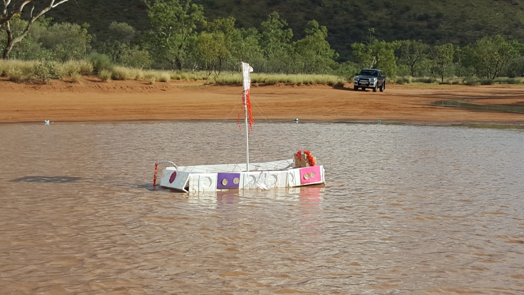 A 'boat' made from foam fridge packaging, wool and coloured paper floats in muddy water in Alice Springs