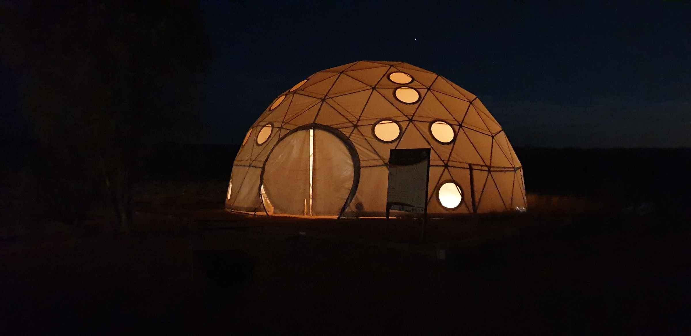 A large domed tent lit up from the inside with circles cut into the panels enabling those inside to view the outside sky.