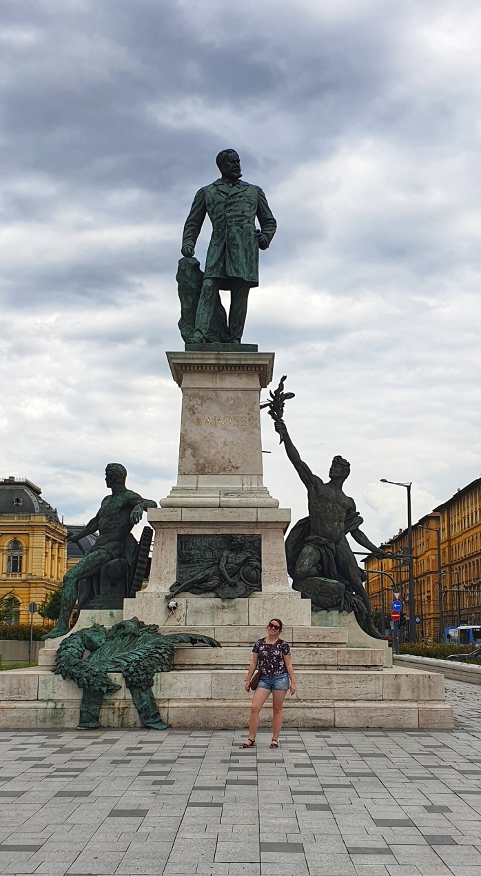 Chasing Emma Standing in front of a statue in Budapest, Hungary.