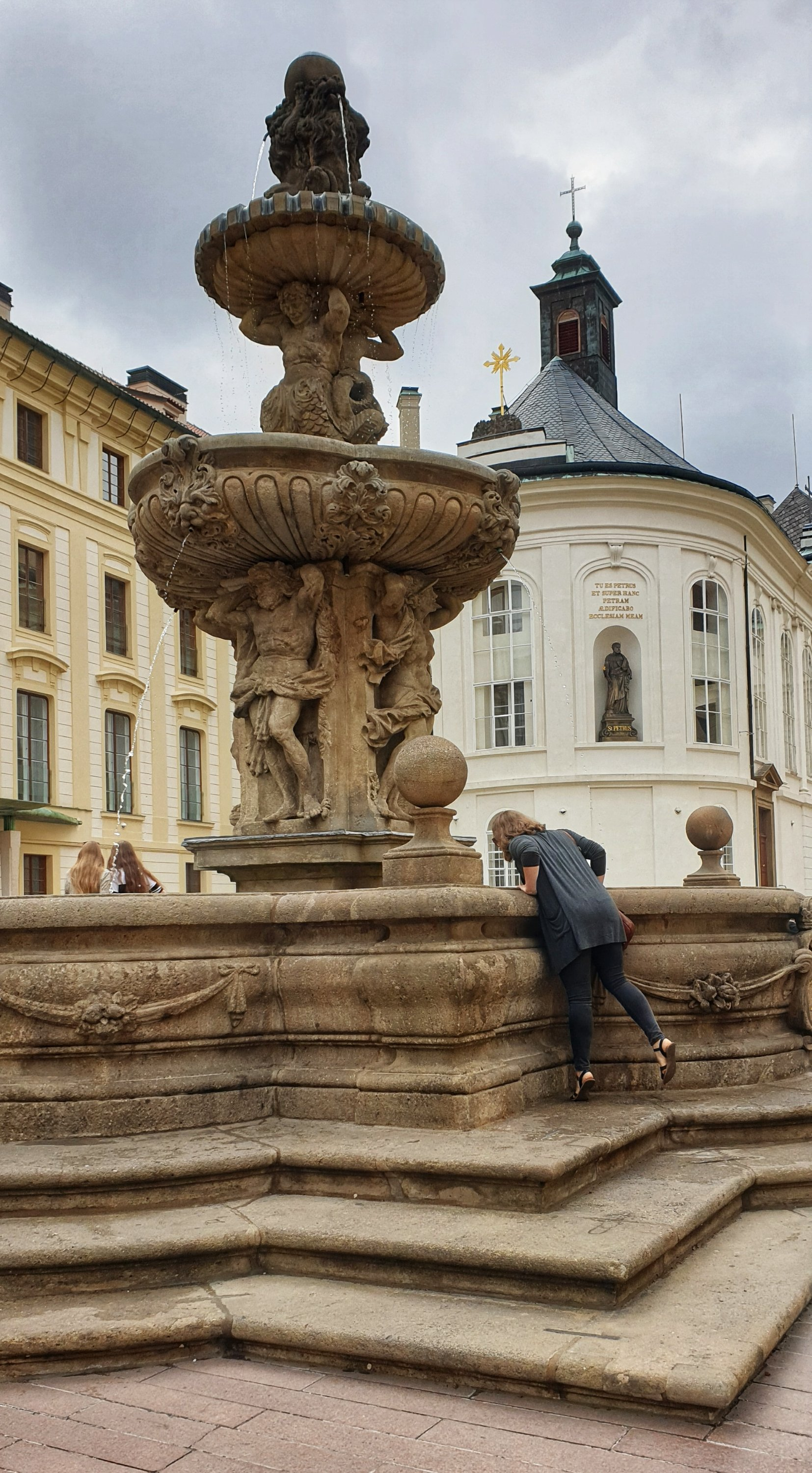 Chasing Emma balanced on one leg looking into a large fountain in the centre of Prague Castle