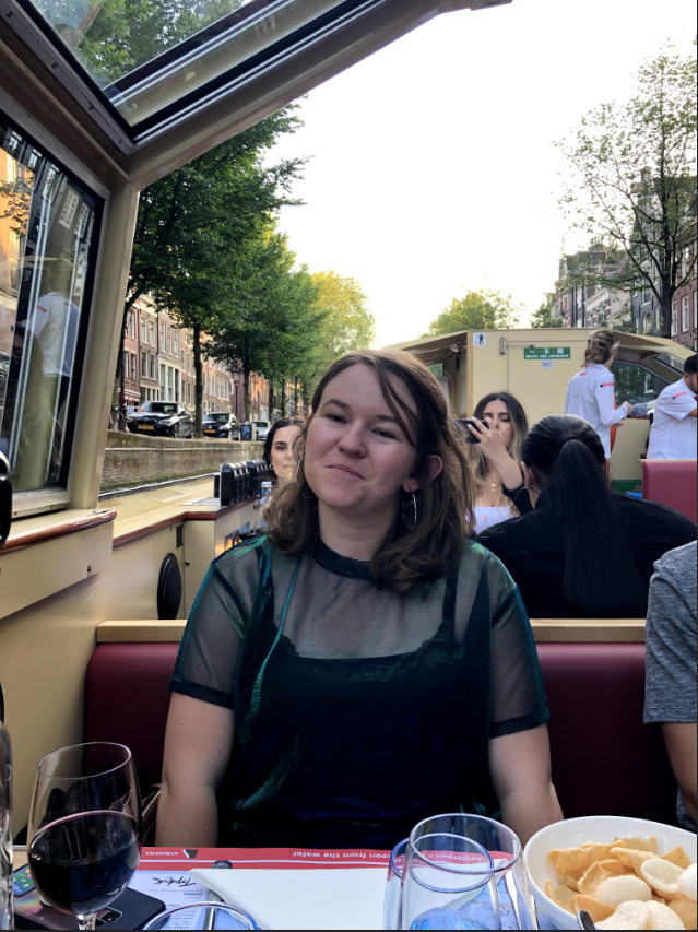 Chasing Emma smiling at the camera while she is on a dinner cruise on the Amsterdam canals