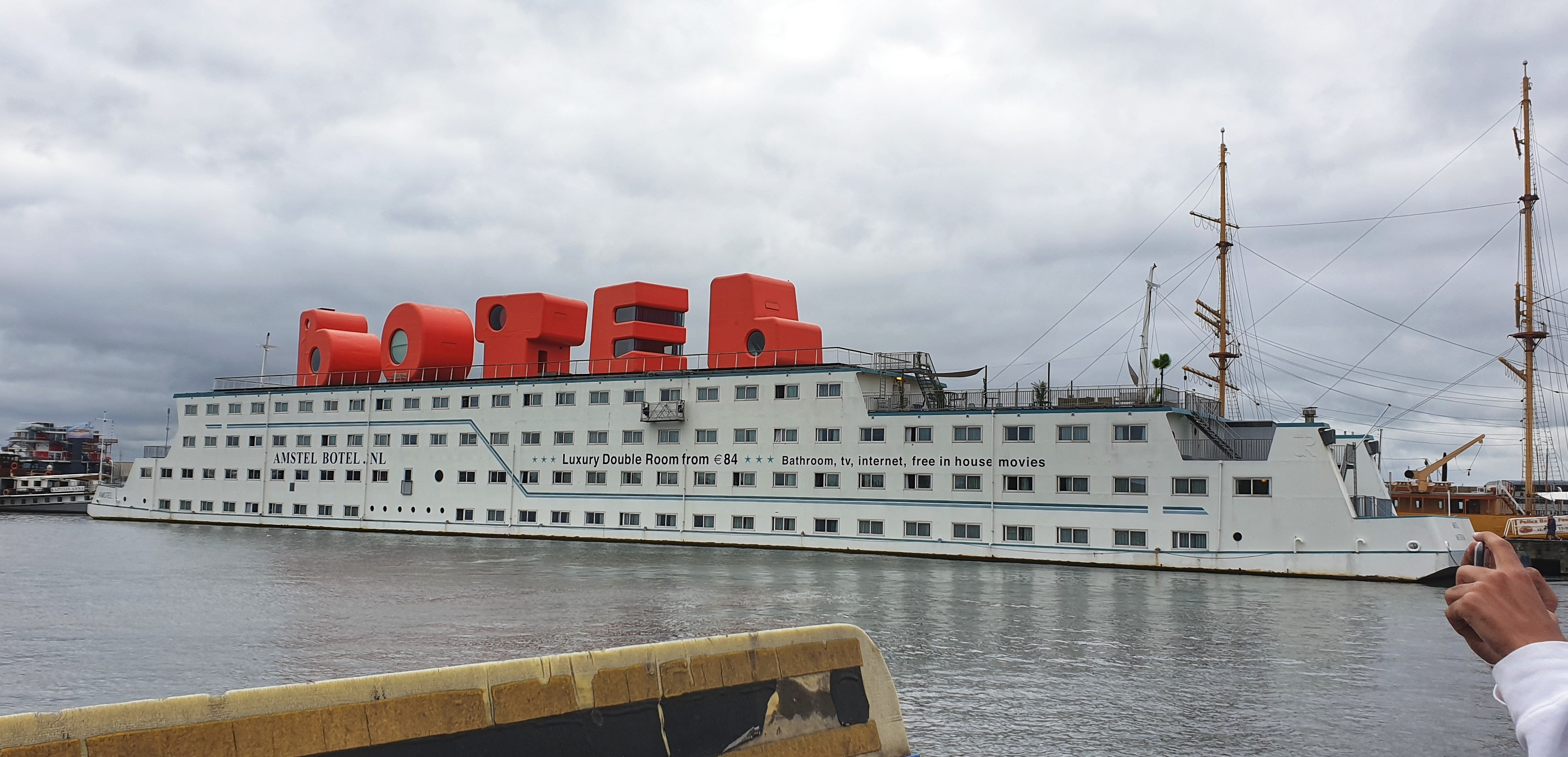 A large white boat with giant orange letters on the roof spelling out B-O-T-E-L