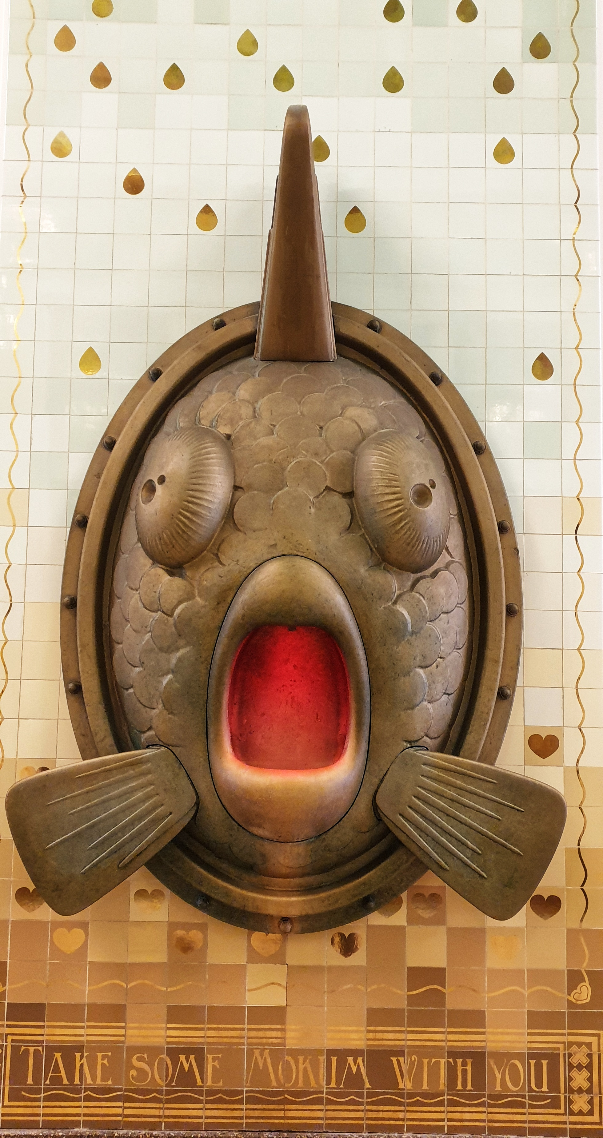 A statue of a fish on a wall in Amsterdam. The fish has i's mouth open in shock.