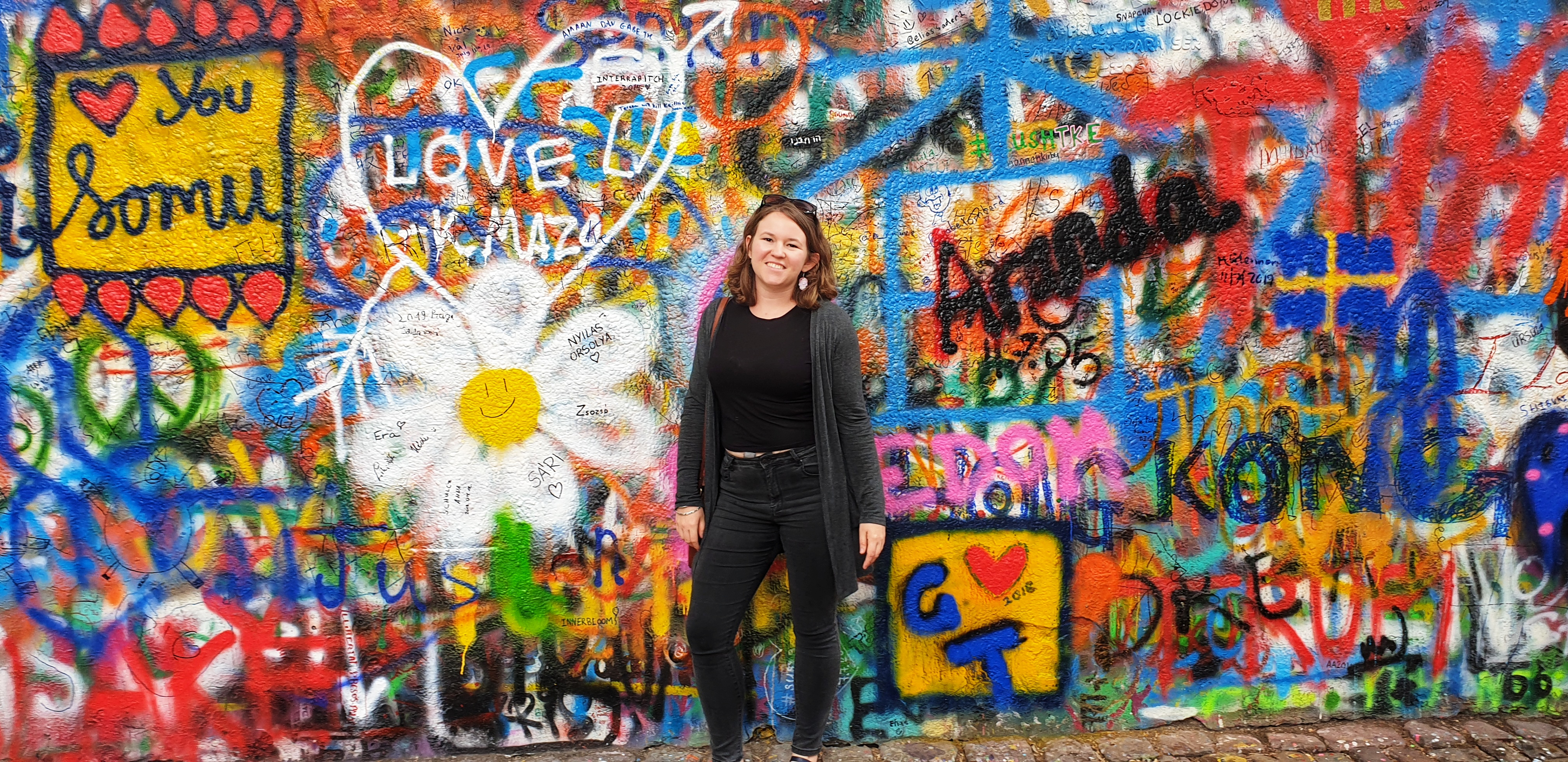 Chasing-Emma.com standing in front of the John Lennon Wall, Prague