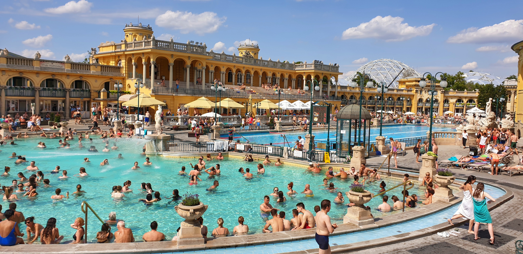 A view of the outdoor baths at Szechenyi. There are a lot of people in each of the baths.
